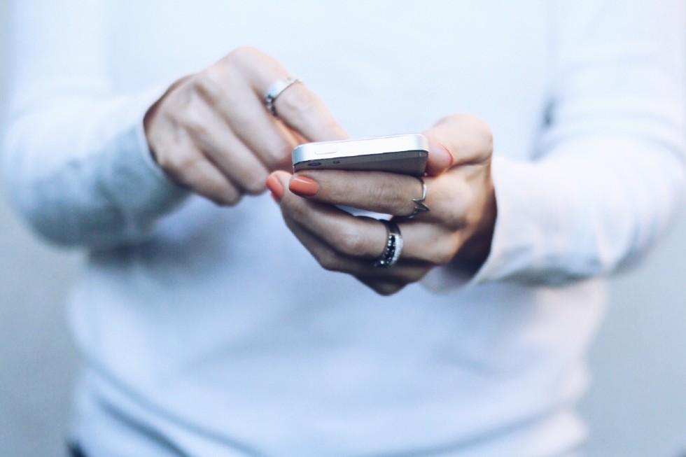 kvinna i vit tröja håller en telefon och knappar på skärmen. Hon bär orange nagellack och bär ringar på fingrarna